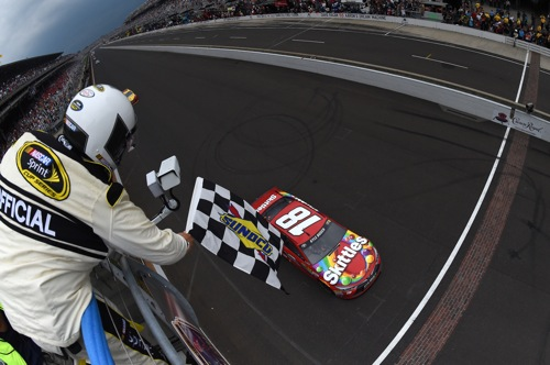 Kyle Busch takes the checkered flag in the Crown Royal Presents the Jeff Kyle 400 at the Brickyard at Indianapolis Motor Speedway on July 26, 2015 (photo courtesy of Getty Images for NASCAR).