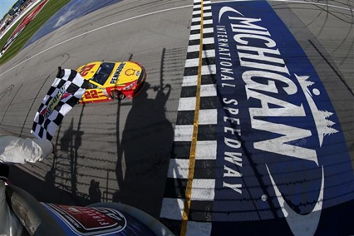 Joey Logano takes the checkered flag in the FireKeepers Casino 400 at Michigan International Speedway on June 12, 2016 (photo courtesy of Getty Images for NASCAR).