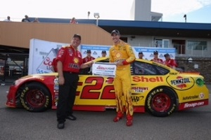 Joey Logano (right) celebrates winning the pole for the Pure Michigan 400 at Michigan International Speedway on Aug. 26, 2016 (photo courtesy of Getty Images for NASCAR).