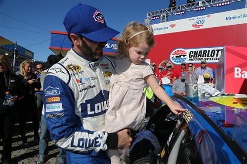 Jimmie Johnson celebrates with his daughter after winning the Bank of America 500 at Charlotte Motor Speedway on Oct. 9, 2016 (photo courtesy of Getty Images for NASCAR)
