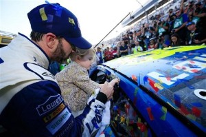 Jimmie Johnson, with the help of his daughter, applies a winner decal to his car after winning the Goody's Fast Relief 500 at Martinsville Speedway on Oct. 30, 2016 (photo courtesy of Getty Images for NASCAR).