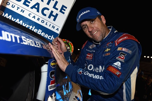 Elliott Sadler applies a winner's decal to his car after winning at Kentucky Speedway on Sept. 24, 2016 (photo courtesy of Getty Images for NASCAR).