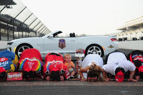 Kyle Busch and his No. 18 Joe Gibbs Racing team celebrate winning the 2016 Brickard 400 by kissing the yard of bricks at the Indianapolis Motor Speedway start/finish line (photo courtesy of Getty Images for NASCAR).