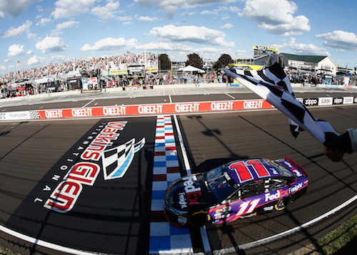 Denny Hamlin takes the checkered flag at Watkins Glen International in 2016 (photo courtesy of Getty Images for NASCAR).
