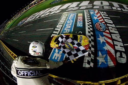 Joey Logano takes the checkered flag in the 2016 NASCAR Sprint All-Star Race at Charlotte Motor Speedway on May 21, 2016 (photo courtesy of Getty Images for NASCAR).