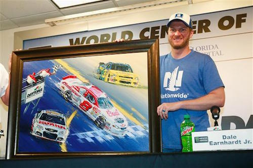 Dale Earnhardt Jr. receives a painting commemorating highlights of his NASCAR racing career at Daytona International Speedway during a press conference at the track on June 30, 2017 (photo courtesy of Getty Images for NASCAR).