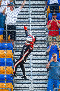 Helio Castroneves, driver of the #3 Hitachi Team Penske IndyCar Chevrolet V6 climbs the fence after racing to victory Sunday July 9, 2017, winning the Verizon IndyCar Series Iowa Corn 300 at Iowa Speedway in Newton, Iowa. The win is the first for Castroneves this season and the 30th of his career. (Photo by Phillip Abbott/LAT for Chevy Racing)