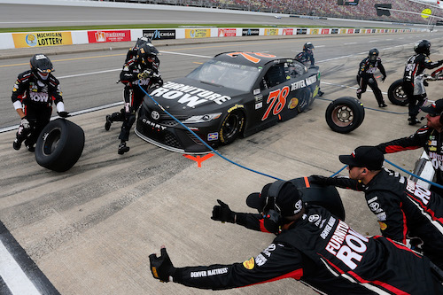 The No. 78 Furniture Row Racing pit crew of Martin Truex Jr. performs a routine pit stop during the Pure Michigan 400 at Michigan International Speedway on Aug. 13, 2017 (photo courtesy of Getty Images for NASCAR).