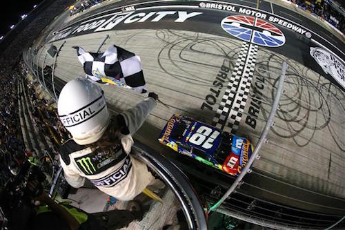 Kyle Busch takes the checkered flag to win the Bass Pro Shops NRA Night Race at Bristol Motor Speedway on Aug. 19, 2017 (photo courtesy of Getty Images for NASCAR).