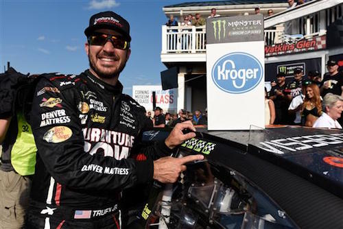 Martin Truex Jr. applies the fourth winner sticker to his No. 78 Furniture Row Racing Toyota after winning the I Love New York 355 at Watkins Glen International on Aug. 6, 2017 (photo courtesy of Getty Images for NASCAR).
