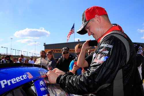Ryan Preece applies a winner's sticker to his Joe Gibbs Racing ride at Iowa Speedway after winning the U.S. Cellular 250 on July 29, 2017 (photo courtesy of Getty Images for NASCAR).