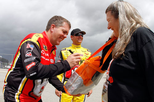 Shane Wilson (left) with Monster Energy NASCAR Cup Series driver Clint Bowyer and a fan in 2011 (photo courtesy of Getty Images for NASCAR).