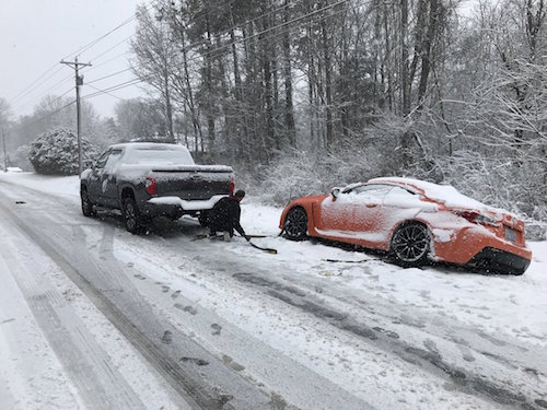 NASCAR driver Daniel Suarez's Lexus is pulled by a truck after sliding off a snowy road in North Carolina on Jan. 17, 2018 (photo courtesy of Daniel Suarez via Twitter).