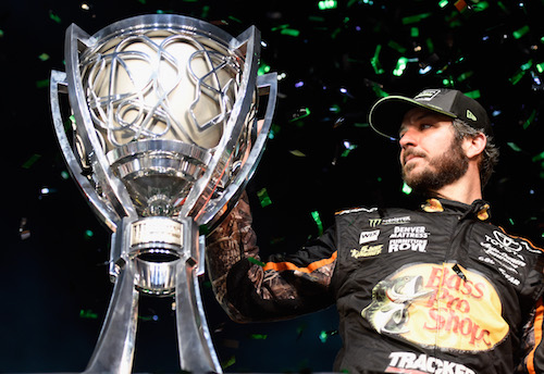 Martin Truex gazes at his 2017 Monster Energy NASCAR Cup Series championship trophy after winning the Ford EcoBoost 400 at Homestead-Miami Speedway on Nov. 19, 2017 (photo courtesy of Getty Images for NASCAR).